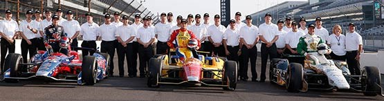 Race teams and drivers posing with 3 open wheel racecars
